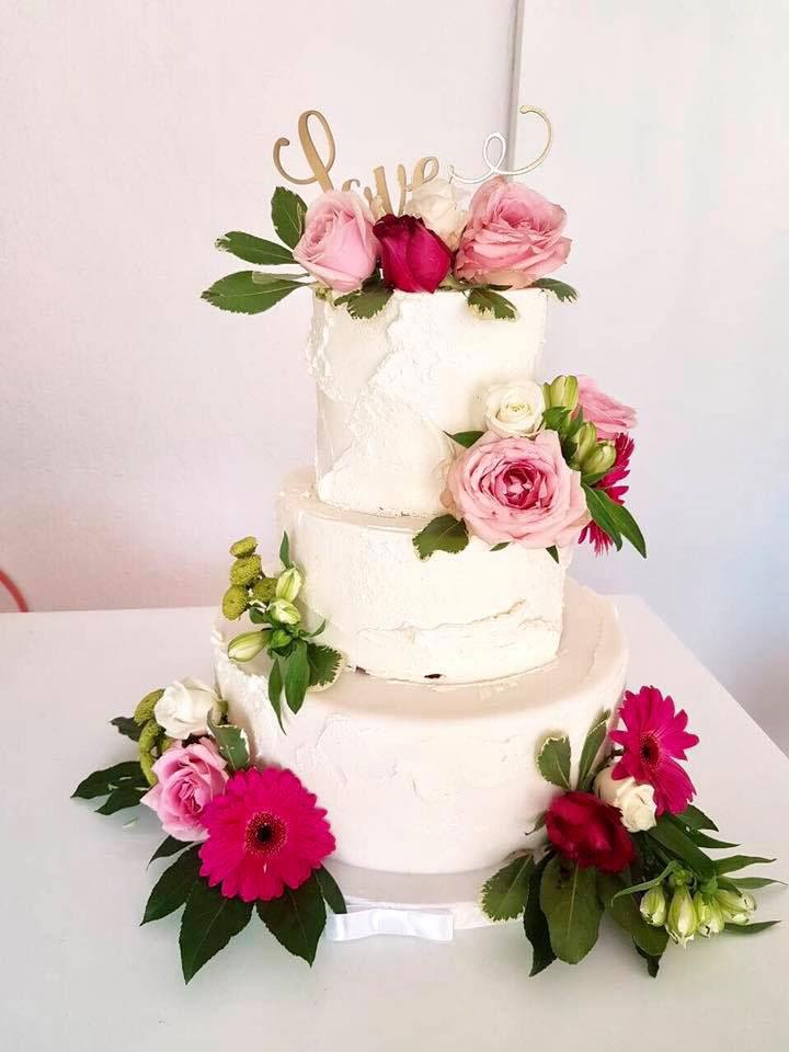 Vit bröllopstårta med färska blommor